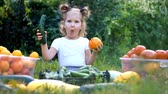 полезный : Child girl eating vegetables. Harvest of farming. The baby is vegan. Vegetarian food. Ripe tomatoes, zucchini and cucumbers Стоковые видеозаписи