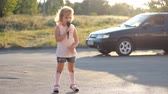 oeuvre : Child girl sings into a microphone a song in the rays of a sunset in the summer. Talented child is a musical voice.
