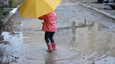 à prova d'água : Funny child girl jumping and playing in puddles in rainy weather under an umbrella