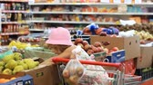 депо : Child girl in the store chooses fruit pears. Grocery supermarket and shopping trolley Стоковые видеозаписи