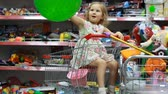 harcamak : Childrens shop with toys. A child in a supermarket sits in the shopping cart