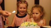 gratulál : Girls sister on a childs birthday. Children watch candles on a cake Stock mozgókép