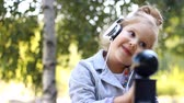 chant : Cute child girl in headphones listening to music and singing a song in a park with birches.