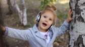 oeuvre : Cute child girl in headphones listening to music and singing a song in a park with birches Stock Footage