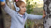 chant : Baby girl in headphones listening to music and singing a song in a park with birches