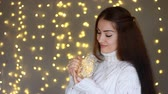 interni casa : New Year. Christmas. Beautiful woman in a warm white sweater holds in hands a lamp, closes his eyes and dreaming on the background of lights.