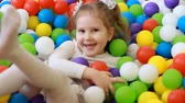 çiğnemek : Happy child girl playing and hiding on the playground with multicolored balloons