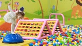 çiğnemek : Child jumping in colorful balloons on the playground. Little girl playing games Stok Video