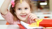 çiğnemek : Child girl eating fast food french fries in a cafe. Portrait closeup Stok Video