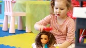 obter : Child playing with doll on the playground. Baby girl plays in the games for children.Mothers Daughter Game