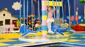 çukur : Child girl playing on carousel on the playground. Baby plays in the room for games Stok Video