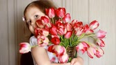 cheirando : Happy baby girl with a bouquet of red tulips . Child sniffs the scent of a tulip. Concept of birthday and mothers day