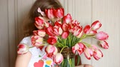 cheirando : Sad child is offended and hides behind a bouquet of tulips. Baby expresses offense. Vídeos