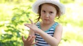 Baby girl in a tropical park puts a cream mosquito repellent on the body and face