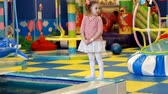 Child girl playing on the playground. Baby plays in the room for games Wideo