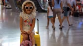 dokumentum : Baby girl tourist is sitting on a big yellow suitcase on train station. Child is waiting for departure on a trip at the airport. Waiting for travel.