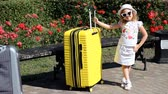 Baby girl tourist with big yellow suitcase. Child waiting for travel.