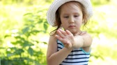 Baby girl in forest puts a cream mosquito repellent on the body and face Vídeos