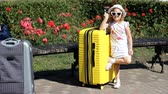 Child tourist with big yellow suitcase. Baby girl waiting for travel. Vídeos