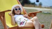 Tourist baby girl is sitting on a deck chair. Baby girl with sunglasses and a hat eats cand y and relaxes on a journey