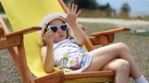 Tourist baby girl is sitting on a deck chair. Baby girl with sunglasses and a hat eats cand y and relaxes on a journey.