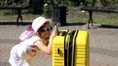 Heavy luggage. Child tourist with big yellow suitcase. Baby girl waiting for travel. Vídeos