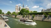 francouzština : PARIS, FRANCE - JUNE 5, 2017: Ship passing by the Seine river past the Notre Dame de Paris cathedral daylight tilt and pan video