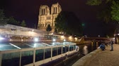 exteriér budovy : PARIS, FRANCE - JUNE 5, 2017: Ship passing by the Seine river the Notre Dame de Paris cathedral twilight tilt and pan video