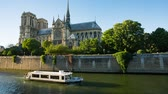 paryż : PARIS, FRANCE - JUNE 10, 2017: Ship passing by the Seine river past the Notre Dame de Paris cathedral