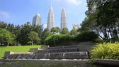 shopping street : Kuala Lumpur, Malaysia - April 19, 2015: Park fountain with Petronas Twin towers on background, View from Kuala Lumpur central park, KLCC