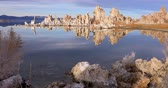 Mono lake tufas with reflection in calm water on sunrise with zoom in effect