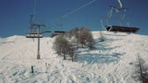 first : Riding a chair lift in first person view above the ski slope on sunny winter day. Stock Footage