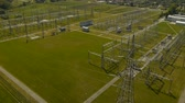 transformador : Detail tilt up aerial view of power substation with green hills at background on sunny summer day. Vídeos