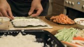 cutting in : Close-up of chef hands cooking and preparing Asian food and sushi in restaurant kitchen. Stock Footage