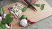 vegetable : Female hand cut kaffir lime leaves in piece on bamboo wooden plate with other Thai herbs beside for Tom Yum recipe. Stock Footage