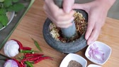 шалот : A female hand pounding many kinds of herbs in mortar to make Thai red curry chili paste or Panang. Стоковые видеозаписи