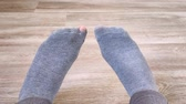 양말 : Female feet in gray worn socks move fingers on floor. Holey sock. Close-up. Shooting on bright day