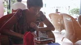 ротанг : Woman sitting in cafe and swiping screen of tablet. Cambodia. Стоковые видеозаписи