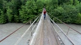 мутный : SVANETI, GEORGIA - May 01, 2017. Tourist with camera on swinging suspension bridge over a mountain river.