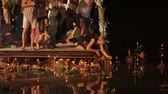loi krathong : PHUKET, THAILAND - November 28, 2012. Locals and tourists celebrating Loi Krathong. People lowered into the water wreaths with candles and let go to heaven Chinese paper lanterns. Stock Footage