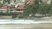 nai harn : PHUKET, THAILAND - November 19, 2012. People bathing in waves and walking on Nai Harn beach..