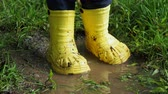 mischief : Little child in bright yellow rubber boots splashing in a puddle. Kids feet protected from dirty water.
