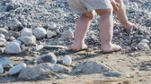 навыки : Baby playing with stones on beach. Kids hands full with sand. Outdoor games.