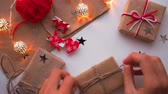 raptiye : Woman is wrapping present box with craft paper and red paper clip. Christmas and New Year background with DIY girts.