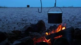 уголь : Cooking soup on a fire pot. Summer camping on beach. Kenozero national park, Russia.