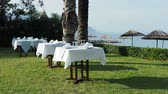 준비하기 : Tables, served for dinner on green lawn. Open air mediterranean meal under palms. Dinner on seaside. 무비클립