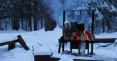 kamp ateşi : Cooking soup on a fire pot. Melting snow as water for tea. Winter camping in forest. Stok Video