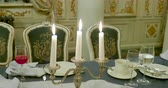staromódní : Burning candles in metal candle holder. Table served for dinner. Beautiful interior detail for party at night.