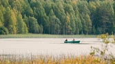 halászat : Two man fishing on boat. Kenozerskiy national park, Russia.