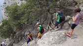 SUDAK, CRIMEA - September 24, 2015. Tourists are climbing down Caraul-Oba mountain. Non-professional hiking without special equipment.